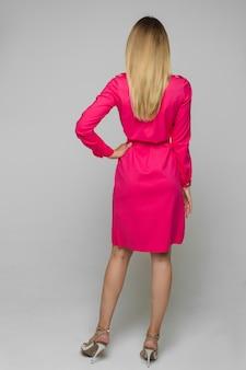 Pełna długość pień fotografia nierozpoznawalnej modelki pozującej w jasnoróżowej sukience z paskiem i modnymi szpilkami z dżetów w studio. widok z tyłu blondynka w sukience z ręką na talii.