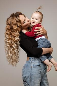 Pełna długość pień fotografia przepięknej blond matki rasy kaukaskiej w swetrze i podarte dżinsy i trampki trzymając jej córeczkę w ramionach, uśmiechając się do kamery.