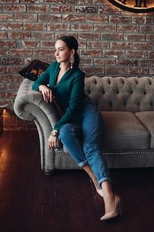 Pełna długość pień fotografia przepięknej brunetki w eleganckich ubraniach i butach na wysokich obcasach, relaksującej się na klasycznej sofie z poduszkami i odwracającej wzrok. pokój urządzony jest w stylu loftu.