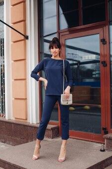 Pełna długość pień fotografia seksownej oszałamiającej kobiety z kok i frędzlami w swobodnym niebieskim garniturze i wysokich obcasach z torebką crossbody stojącą na ganku.