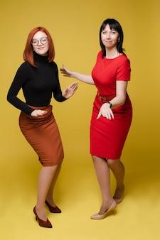 Pełna długość pień fotografia wesołych dorosłych kobiet w sukienkach i szpilkach tańczących i bawiących się w studio. wyizoluj na jasnożółtym tle.
