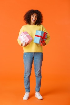 Pełna długość pionowa podekscytowana urocza szczęśliwa afroamerykańska kobieta otrzymała prezenty na wakacje, stojąc rozbawiona i zachwycona, trzymając dwa zapakowane prezenty, pomarańczowa