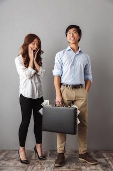 Pełna długość podekscytowanej azjatyckiej pary stojącej, trzymającej teczkę pełną banknotów pieniędzy