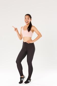 Pełna długość podekscytowanej uśmiechniętej atletki w odzieży sportowej wyglądającej na zdumioną i wskazującej palcem w lewo, atletka ciesząca się fitnessem na siłowni, zaprasza nowych członków.