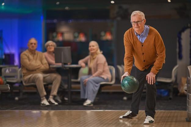 Pełna długość portret aktywnego starszego mężczyzny grającego w kręgle z grupą przyjaciół w tle, kopia przestrzeń