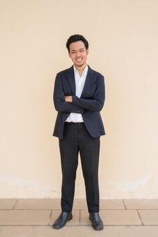 Pełna długość portret azjatyckiego biznesmena w garniturze na prostym tle z rękami skrzyżowanymi podczas uśmiechu