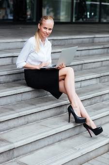 Pełna długość portret blond businesswoman pisania na laptopie whie siedzącej na schodach na zewnątrz
