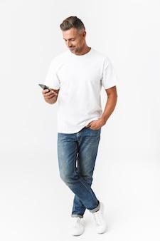 Pełna długość portret brunetki mężczyzny w wieku 30 lat w swobodnym t-shirt i dżinsach przy użyciu telefonu komórkowego, trzymając w ręku na białym tle