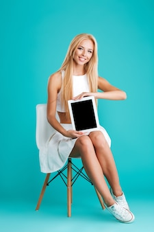 Pełna długość portret całkiem młodej kobiety pokazującej pusty ekran tabletu siedząc na krześle na białym tle na niebieskim tle