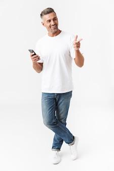 Pełna długość portret dojrzałego mężczyzny w wieku 30 lat w swobodnym t-shirt i dżinsach przy użyciu telefonu komórkowego, trzymając w ręku na białym tle