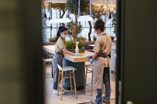 Pełna długość portret dwóch pracownic noszących maski podczas czyszczenia stołów w nowoczesnym wnętrzu kawiarni, koncepcja bezpieczeństwa covid