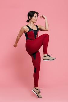 Pełna długość portret fit pięknej sportowej kobiety wykonującej ćwiczenia izolowane nad różową ścianą, skakanie