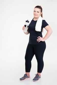 Pełna długość portret grubej kobiety w stroju sportowym, trzymając shaker na białym tle na białej ścianie