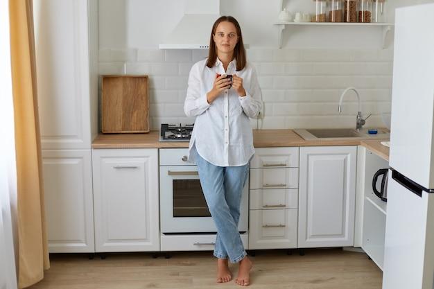 Pełna długość portret kobiety picia kawy rano w domu, stojąc w pobliżu zestawu kuchennego, ciesząc się gorącym napojem w domu, ubrana w białą koszulę i dżinsy.