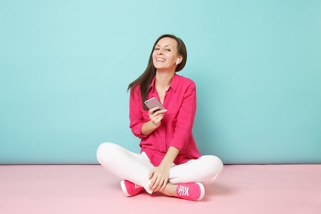 Pełna długość portret kobiety w różowej koszulowej bluzce, białych spodniach siedzących na podłodze ze słuchawkami