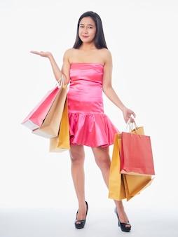 Pełna długość portret kobiety w różowej sukience z torbami na zakupy na białym tle