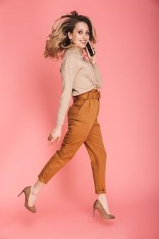 Pełna długość portret ładnej kobiety w wieku 30 lat z blond włosami, uśmiechniętej i spacerującej na różowo