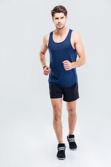 Pełna długość portret mężczyzny fitness działa na białym tle na białym tle