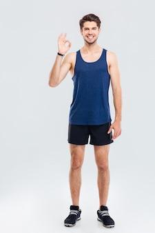 Pełna długość portret mężczyzny fitness pokazując znak porządku na białym tle na szarym tle