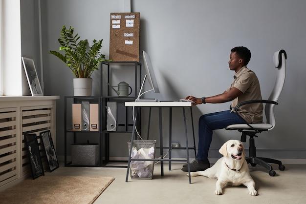 Pełna długość portret młodego afroamerykańskiego mężczyzny pracującego w biurze z psem na podłodze, obszar roboczy przyjazny dla zwierząt, kopia przestrzeń