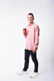 Pełna długość portret młodego człowieka, uśmiechając się i pije filiżankę kawy na wynos.