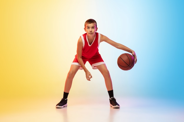 Pełna długość portret młodego koszykarza w mundurze na ścianie gradientowej