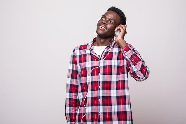 Pełna długość portret młodego mężczyzny afro american słuchanie muzyki w słuchawkach na białym tle