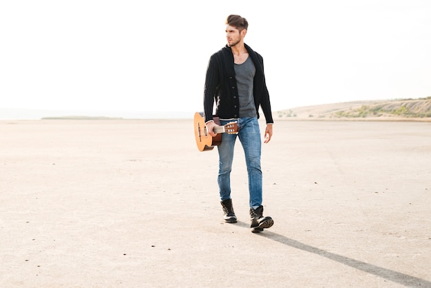 Pełna długość portret młodego mężczyzny dorywczo spacerującego po brzegu morza z gitarą