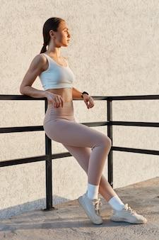 Pełna długość portret młodej atrakcyjnej kobiety z pewnym siebie wyrazem twarzy, ubrana w biały top i beżowe legginsy
