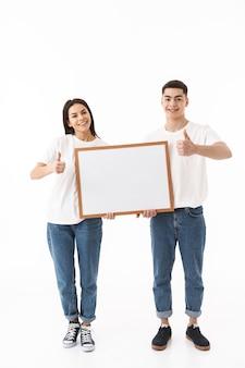 Pełna długość portret młodej atrakcyjnej pary stojącej na białym tle nad białą ścianą, przedstawiającej pustą deskę, kciuk w górę