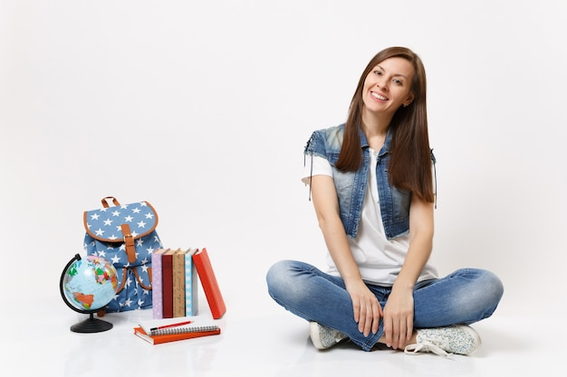 Pełna długość portret młodej dorywczo uśmiechniętej studentki w dżinsowych ubraniach siedzącej w pobliżu plecaka na świecie, izolowane podręczniki szkolne