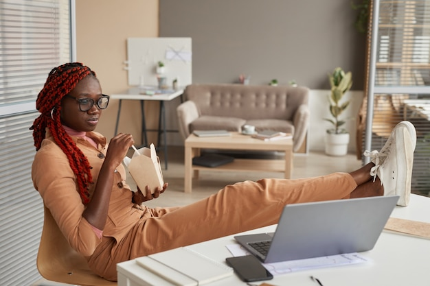 Pełna długość portret młodej kobiety african-american jedzenia na wynos i patrząc na ekran laptopa, relaksując się w domowym biurze, kopia przestrzeń