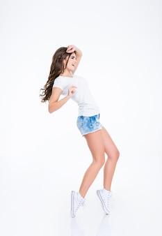 Pełna długość portret młodej kobiety tańczącej na białym tle na białej ścianie