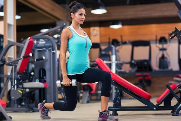 Pełna długość portret młodej kobiety treningu z hantlami w siłowni fitness