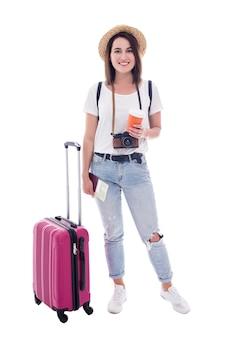 Pełna długość portret młodej kobiety turysty z walizką, aparatem, paszportem, mapą i filiżanką kawy na białym tle