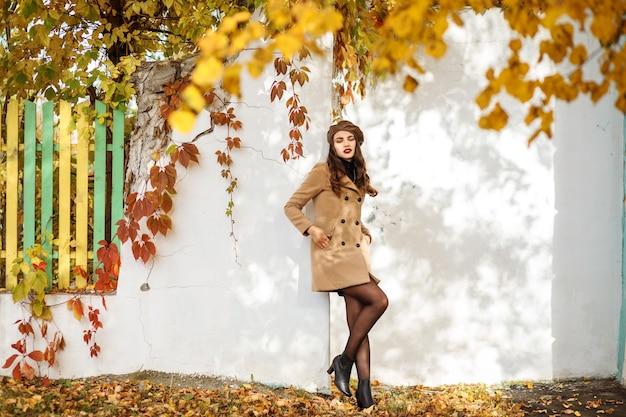 Pełna długość portret modnej kobiety ubranej w beżowy płaszcz brązowy beret spędza czas na świeżym powietrzu jesienią