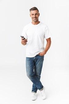 Pełna długość portret muskularnego mężczyzny w wieku 30 lat w swobodnym t-shirt i dżinsach za pomocą telefonu komórkowego, trzymając w ręku na białym tle
