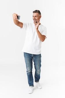Pełna długość portret nieogolony mężczyzna 30s ubrany w casual t-shirt i dżinsy biorąc selfie zdjęcie na telefonie komórkowym, trzymając w ręku na białym tle