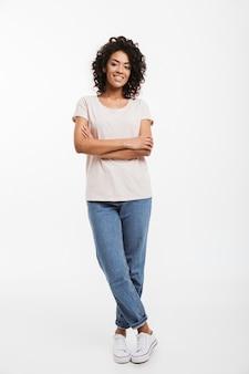 Pełna długość portret pięknej amerykańskiej kobiety w dżinsach i t-shirt stojący z założonymi rękoma i uśmiech, na białym tle nad białą ścianą
