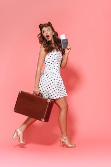 Pełna długość portret pięknej młodej dziewczyny pin-up na sobie sukienkę stojącą na białym tle, pokazując paszport z biletem lotniczym, niosąc walizkę