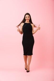 Pełna długość portret pięknej młodej kobiety na sobie czarną sukienkę stojącą na białym tle na różowym tle, pokazując kciuk do góry