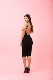 Pełna długość portret pięknej młodej kobiety na sobie czarną sukienkę stojącą na białym tle na różowym tle, pozowanie