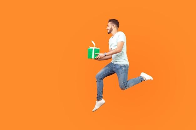 Pełna długość portret podekscytowany szczęśliwy brunetka mężczyzna w trampki i strój dżinsowy, latający lub biegający w powietrzu z pudełkiem prezentowym, prezentem świątecznym, spiesząc się na sprzedaż. studio strzał na białym tle na pomarańczowym tle