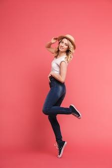 Pełna długość portret pozytywnej blond kobiety w dżinsach i słomkowym kapeluszu, uśmiechniętej i chodzącej na białym tle nad różową ścianą