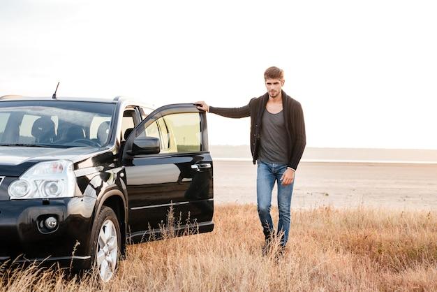 Pełna długość portret przypadkowego młodego mężczyzny stojącego z samochodem zaparkowanym na zewnątrz