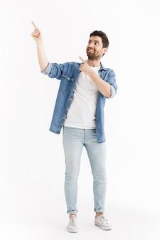 Pełna długość portret przystojnego brodatego mężczyzny noszącego zwykłe ubrania stojącego na białym tle, wskazującego na miejsce kopiowania