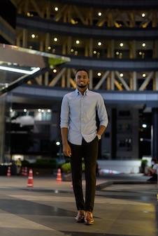 Pełna długość portret przystojnego czarnego afrykańskiego biznesmena na zewnątrz w mieście w nocy pionowe ujęcie