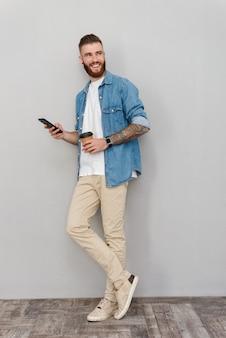 Pełna długość portret przystojnego uśmiechniętego młodego mężczyzny w zwykłych ubraniach, stojącego nad szarą ścianą, używającego telefonu komórkowego podczas picia filiżanki kawy na wynos