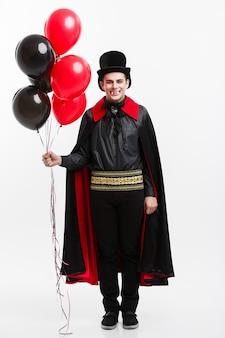 Pełna długość portret przystojny kaukaski wampir w czarnym i czerwonym kostiumie halloween.