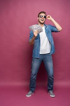 Pełna długość portret radosnego mężczyzny w jeansowej koszuli trzymającego kilka banknotów pieniędzy, stojąc i świętując na białym tle nad różowym tle